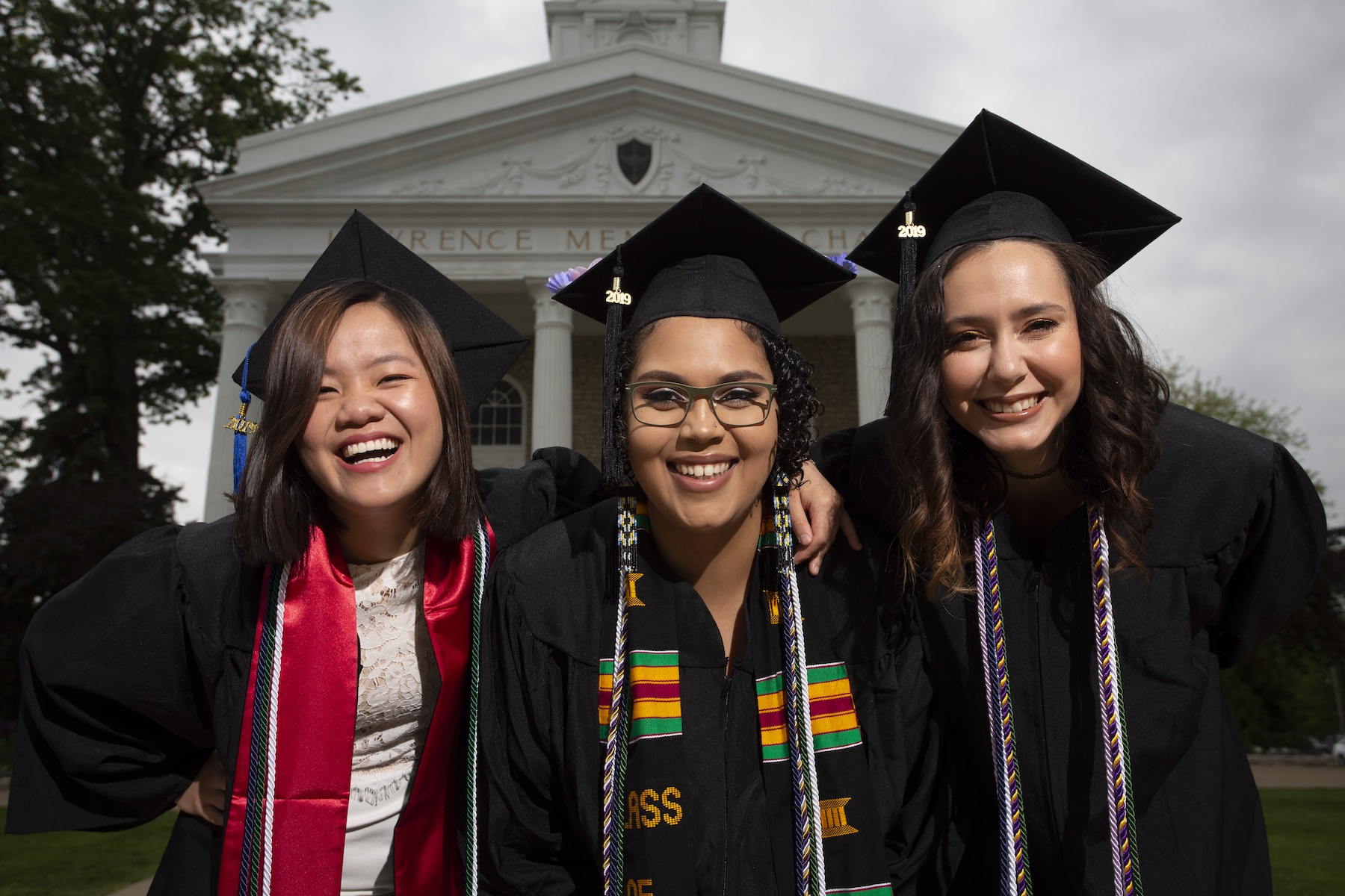 Hoa Huynh, Jordyn Pleiseis, and Miranda Salazar pose in cap and gown in front of Memorial Chapel on Commencement morning.