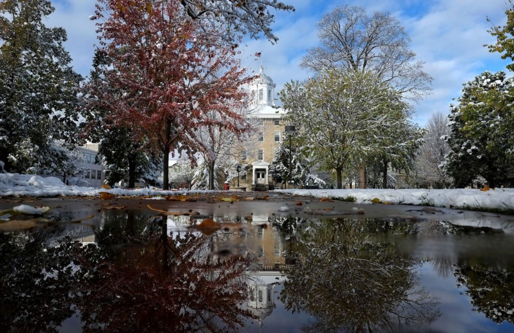 Main Hall is reflected during the first snow fall of the season.