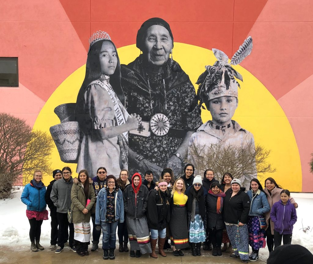 Native students pose in front of the indigenous education mural on the side of the Buchanen Kiewit Wellness Center.