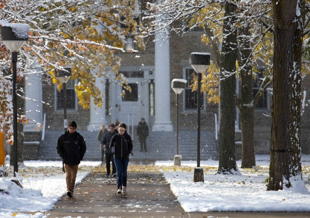 Students walk from Main Hall as snow falls on Main Hall Green.