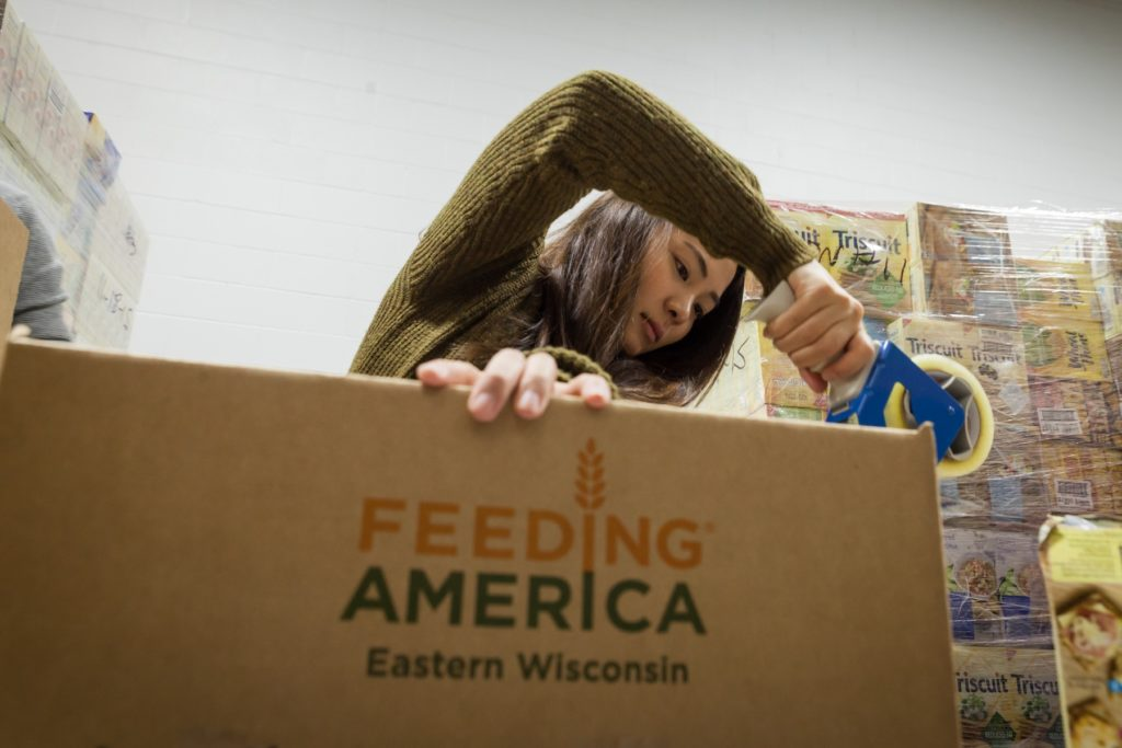 A Lawrence student packages supplies during a volunteer shift at Feeding America.