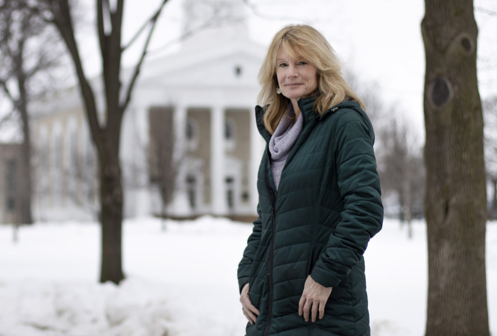 Patty Darling poses for a photo on a snow-covered Main Hall Green, with Main Hall in the background.