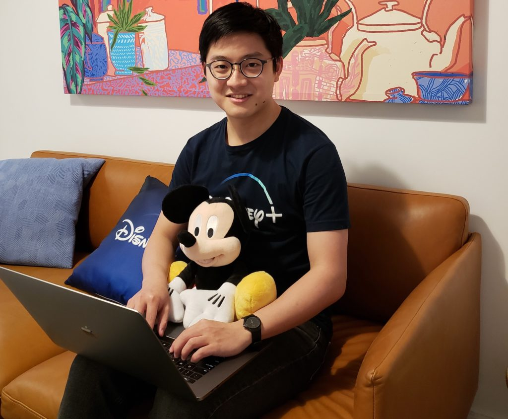 Kir-Sey Fam '19 holds a laptop and a stuffed Mickey Mouse toy at the Disney+ headquarters in New York.
